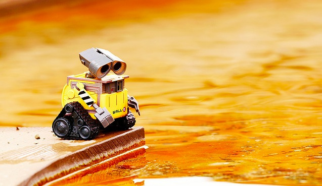 WALL-E looking at a puddle