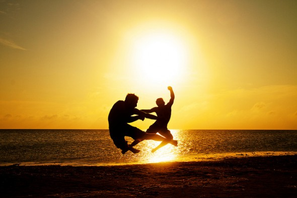 Two people on the beach jumping making ninja poses